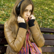 Attractive girl in park listens to music - Stock Photo