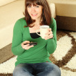 Young woman drinking coffee and talking on the phone — Stock Photo