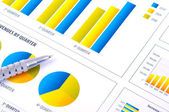 Financial Analysis with charts and metallic pen — Stock Photo