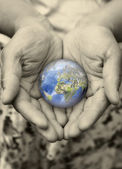 Old hand holding the earth with care — Stock Photo