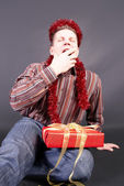 A man yawns, laying a gift on knees — Stock Photo