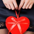 Stock Photo: Sexy womin mini skirt holding Valentine's Day heart