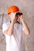 Builder looking through binoculars at the background of the plas — Stock Photo