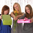 Stock Photo: Young women give gifts and flowers - isolated on white