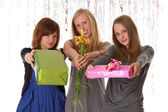 Young women give gifts and flowers - isolated on white — Stock Photo