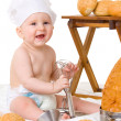 Little baby chef in the cook costume with bread — Stockfoto
