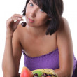 Cheerful woman eating fruit and berrie — Stock Photo