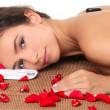 Woman getting spa treatment with black stone and rose petals — Stock Photo