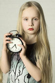 Beautiful girl holding alarm clock — Stock Photo