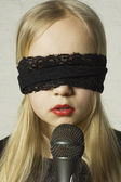 Girl with a black lace blindfold and a microphone. Mystery — Stock Photo