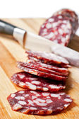 Salami sliced on chopping board — Stock Photo
