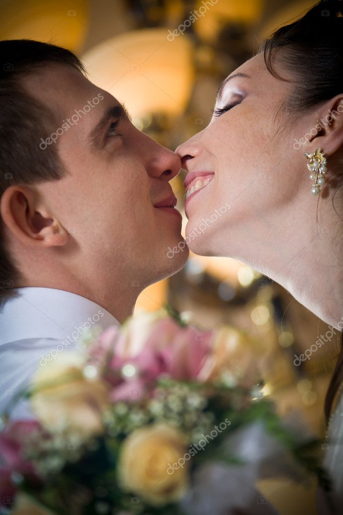 Beautiful young bride kissing groom in decorated indoor setting — Stock Photo #4505179
