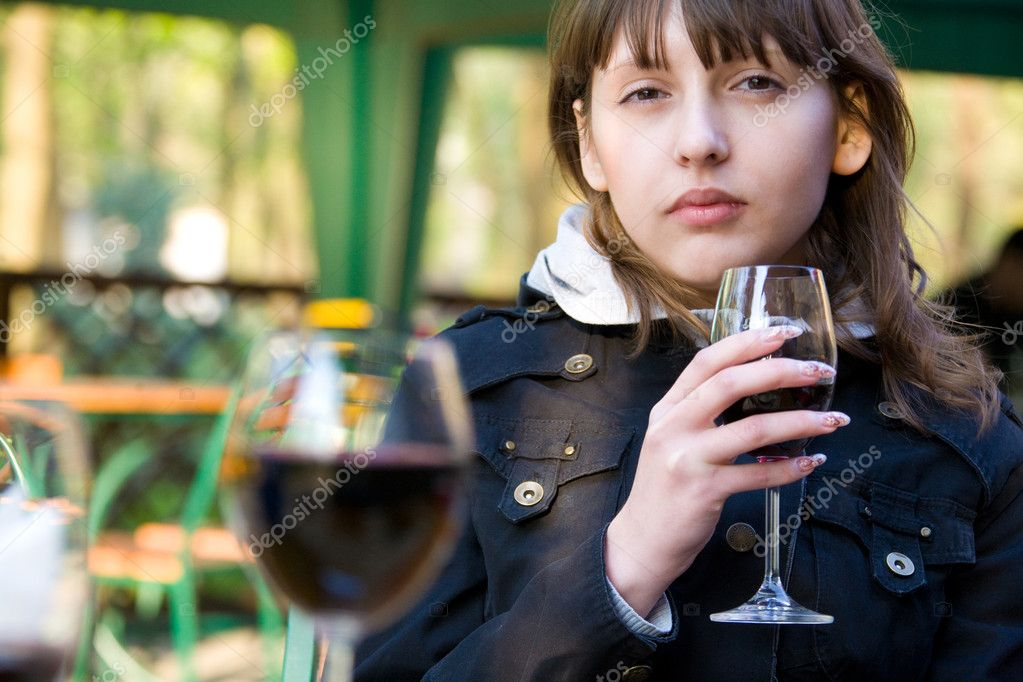 Cute young woman with wine glass sitting in cafeteria — Stock Photo #4505321