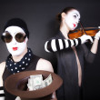 Two mimes playing a violin for the money — Stock Photo