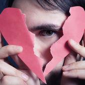 Tvář pohledný mladík s nefunkční papírové srdce — Stock fotografie