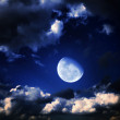 Moon and stars in a cloudy night blue sky — Stok fotoğraf