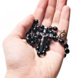 Hand holding wooden rosary with Catholic crucifix — Stock Photo