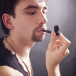 Young man smoking little pipe — Stock Photo