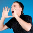 Young man shouting with hands cupped to his mouth — Stock Photo #4004844