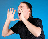 Young man shouting with hands cupped to his mouth — Stock Photo
