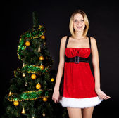 Girl in santa hat about christmas tree. — Stock Photo