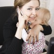 Stock Photo: Busy mother with her baby