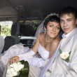 Smiling bride and groom in wedding car — Stock Photo #5249495