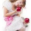 Girl plays with Christmas red ball — Stock Photo #5254800
