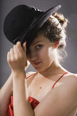 Woman's look at camera. Elegance young woman in a black hat. — Stock Photo