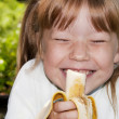 Little girl in the outdoors eats a banana and laughs — Stock Photo #5269765