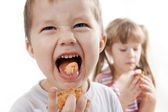 Children eat a cake. — Stock Photo