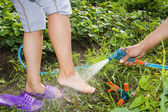 Man waters from a water hose of a foot of the woman in a garden — Stock Photo