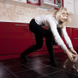 Young woman playing with a kitten on red kitchen — Stock Photo #5331937