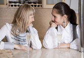 Vrienden meisjes plezier op keuken met een glas alcohol — Stockfoto