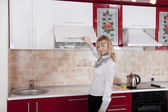 Young woman to kitchen in red-white color — Stock Photo