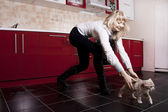 Young woman playing with a kitten on red kitchen — Stock Photo