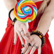 Stock Photo: Young girl is holding lollypop