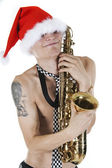 Young Santa embraces a saxophone — Stock Photo