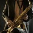 Stock Photo: Young jazzmplaing saxophone on black