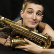 Young jazzmlie on floor with saxophone — Stockfoto #4822752