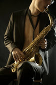 The young jazzman plaing a saxophone on black — Stock Photo