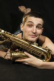 The young jazzman lie on the floor with saxophone — Stock Photo