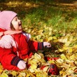 Baby playing with autumn leaves — Stockfoto