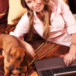 Girl and a computer at home and dachshund — Stock Photo