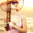 Portrait girl in hat looking through sunglasses — Stock Photo