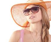 Stående flicka i hatt titta igenom solglasögon — Stockfoto