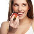 Beautiful girl eating a fresh red strawberry with chocolate sauc — Stock Photo