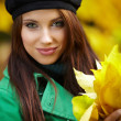 Fashion woman in autumn park holding yellow leaf — Stock Photo #4917632