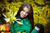 Fashion woman in autumn park holding yellow leaf — Stock Photo