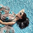 Sexy girl relaxing in a pool - Stock Photo